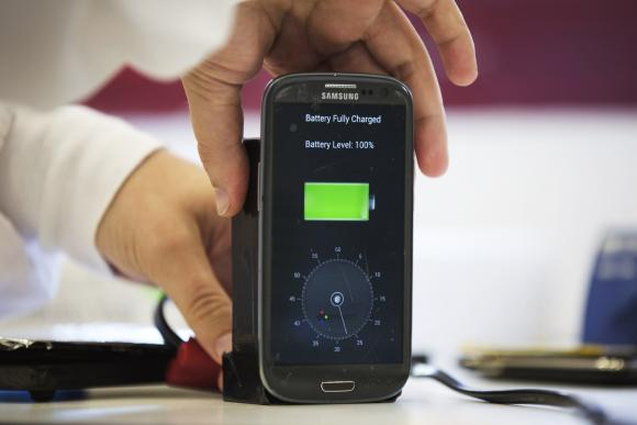 A lab worker disconnects from a charger a mobile phone at headquarters of StoreDot in Tel Aviv